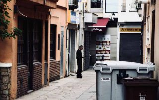 A view of a bin lined alley similar to the one that this couple could see from their hotel room. Certainly not the sea-view they'd been promised!
